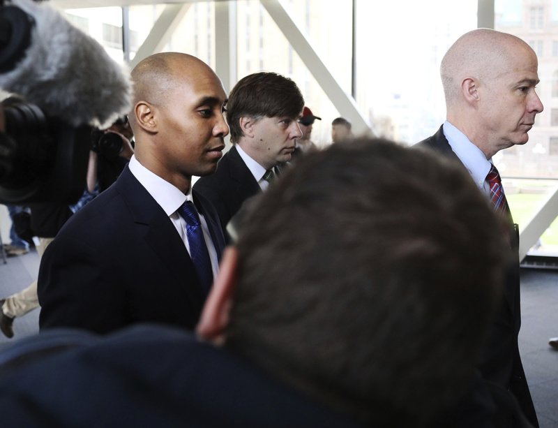 Former Minneapolis police officer Mohamed Noor, center, is accompanied by his attorneys Peter Wold, not pictured, and Thomas Plunkett, right, as he walks towards the Hennepin County Government Center for opening arguments of his trial Tuesday, April 9, 2019, in Minneapolis, Minn. (David Joles/Star Tribune via AP)