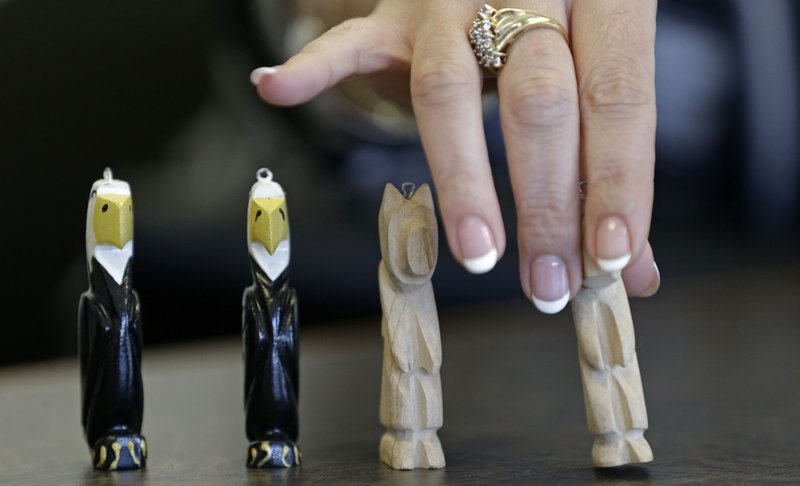 In this photo taken Wednesday, March 6, 2019 in Raleigh, N.C. Heather Allen arranges some carvings made by her father, Lee Wayne Hunt, while he was in prison. (AP Photo/Gerry Broome)