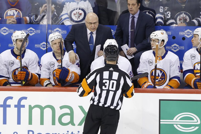 New York Islanders coach Barry Trotz talks to a referee during the first period of the team's NHL hockey game against the Winnipeg Jets on Thursday, March 28, 2019, in Winnipeg, Manitoba. (John Woods/The Canadian Press via AP)