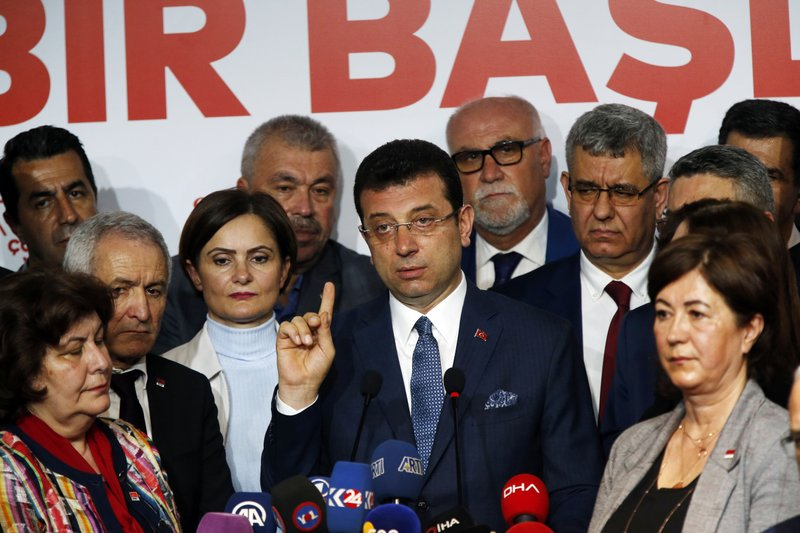 Ekrem Imamoglu, centre, the opposition, Republican People's Party's (CHP) mayoral candidate in Istanbul, talks to members of the media, in Istanbul, Tuesday, April 9, 2019. (AP Photo/Lefteris Pitarakis)
