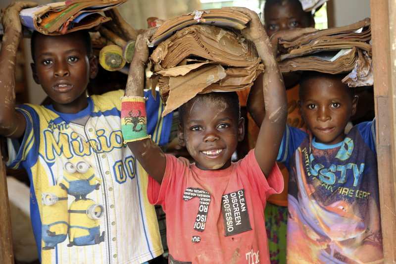 Children carry books damaged by the cyclone at a camp for displaced survivors of cyclone Idai in Dombe, about 280km west of Beira, Mozambique, Thursday, April 4, 2019. (AP Photo/Tsvangirayi Mukwazhi)