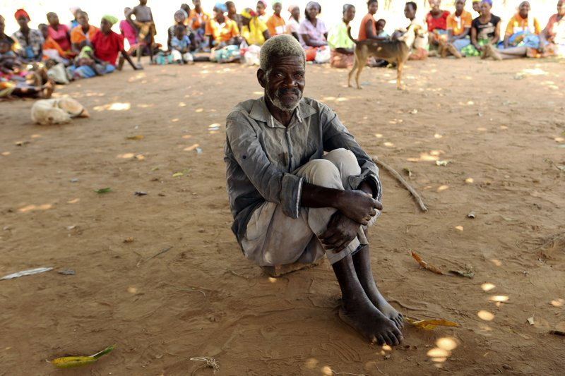 A man waits to receive food aid outside a camp for displaced survivors of cyclone Idai in Dombe, about 280km west of Beira, Mozambique, Thursday, April 4, 2019. (AP Photo/Tsvangirayi Mukwazhi)