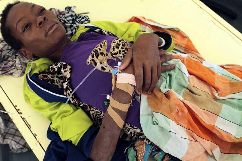 A woman diagnosed with cholera lies on a bed at a treatment centre in Beira, Mozambique, Saturday, March 30, 2019. (AP Photo/Tsvangirayi Mukwazhi)