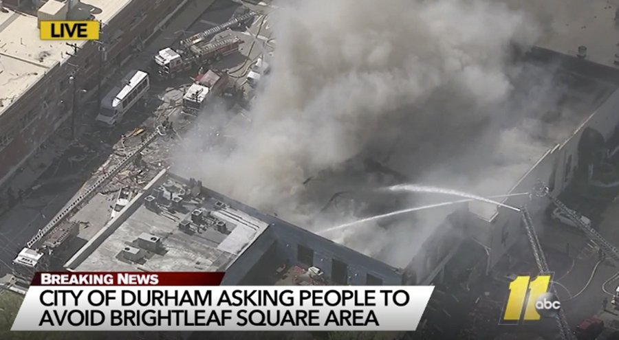 In this image made from video and provided by WTVD-TV Durham, firefighters spray water on a building Wednesday, April 10, 2019, in downtown Durham, N. (WTVD-TV Durham via AP)