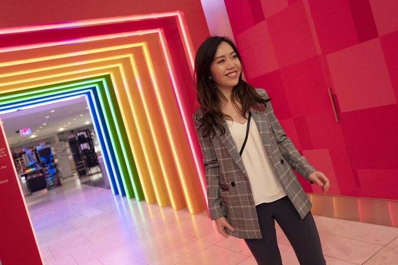 Yoli Ho poses for photos at the entrance to Story on its opening day at Macy's, Wednesday, April 10, 2019, in New York. (AP Photo/Mark Lennihan)