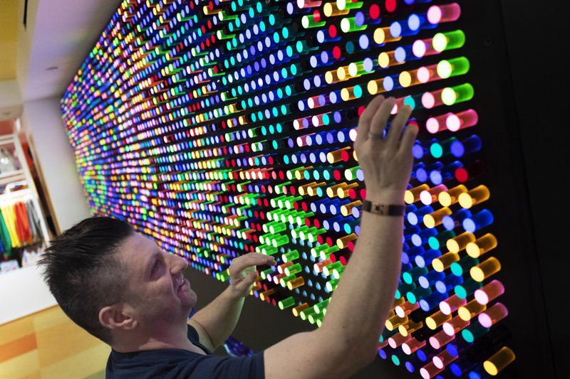 Adam Greenspan, founder and Chief Illumination Officer of LiteZilla, prepares his company's interactive wall in Story, Wednesday, April 10, 2019, at Macy's in New York. (AP Photo/Mark Lennihan)