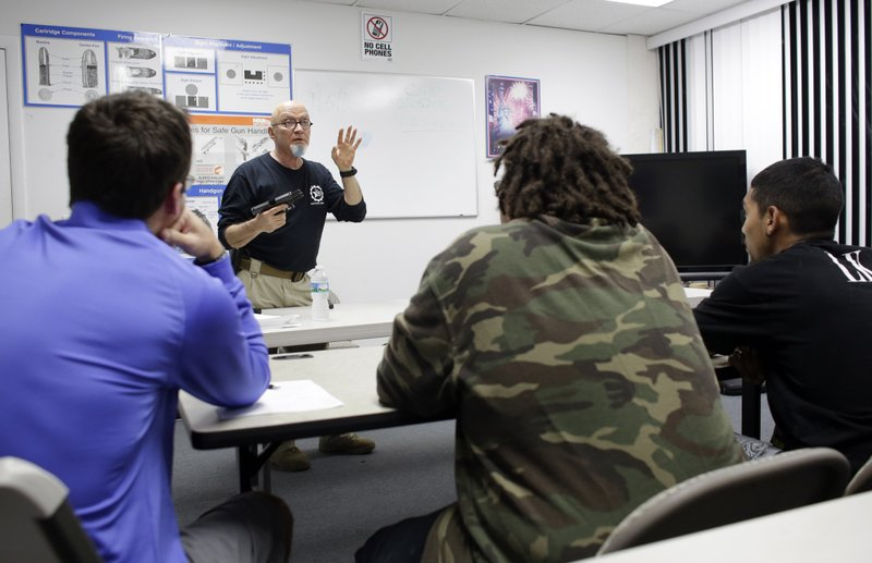FILE - In this Jan. 5, 2016 file photo, Mike Weinstein, director of training and security at the National Armory gun store and gun range, shows how to safely fire a Glock 9mm handgun during a concealed weapons permit class, in Pompano Beach, Fla. (AP Photo/Lynne Sladky, File)