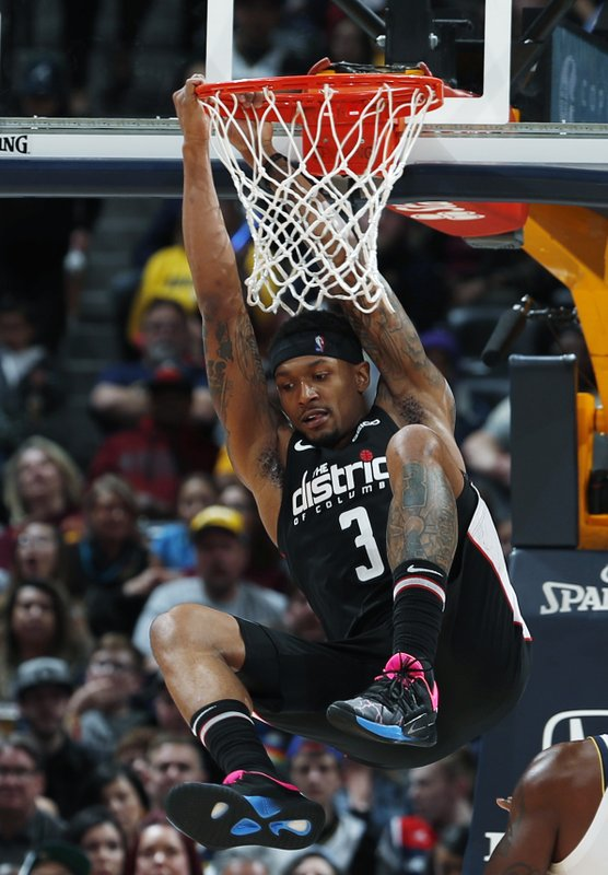Washington Wizards guard Bradley Beal hangs from the rim after dunking the ball for a basket again the Denver Nuggets in the second half of an NBA basketball game Sunday, March 31, 2019, in Denver. (AP Photo/David Zalubowski)