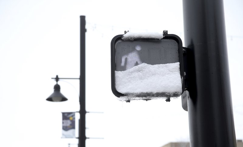 Snow blocks a walking sign after initial snowfall and before a blizzard warning went into effect for southeast Wyoming on Wednesday, April 10, 2019, in Cheyenne. ( Jacob Byk/The Wyoming Tribune Eagle via AP)