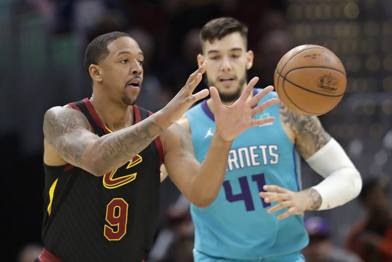 Cleveland Cavaliers' Channing Frye, left, catches a pass against Charlotte Hornets' Willy Hernangomez in the second half of an NBA basketball game, Tuesday, April 9, 2019, in Cleveland. (AP Photo/Tony Dejak)