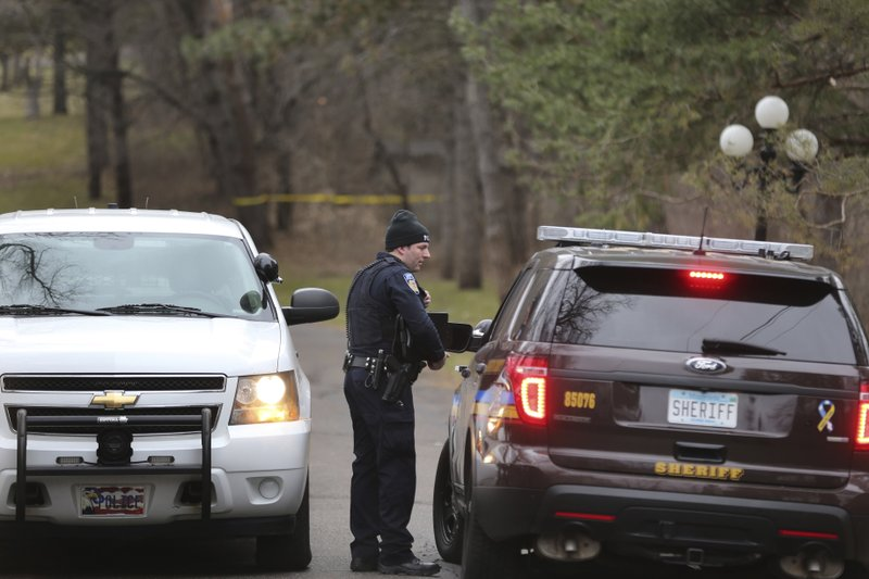 Law enforcement personnel confer outside a home in Orono, Minn., Wednesday, April 10, 2019. Authorities are investigating the deaths of two people found at the Lake Minnetonka mansion of Irwin Jacobs, a prominent Minnesota businessman who once owned a minority share in the Minnesota Vikings NFL team. (Richard Tsong-Taatarii/Star Tribune via AP)