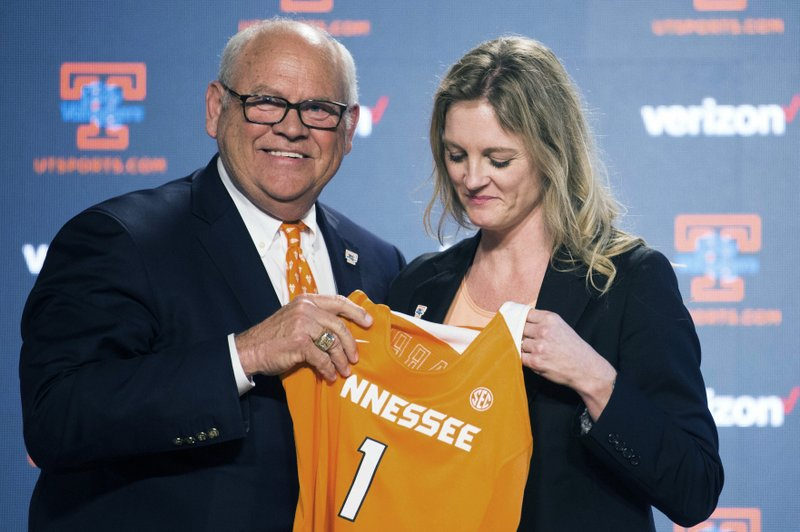 University of Tennessee athletic director Phillip Fulmer passes a jersey to Kellie Harper during a press conference announcing her as the new head coach of the Lady Vols, in the Ray and Lucy Hand Studio on University of Tennessee's campus Wednesday, April 10, 2019 in Knoxville, Tenn. (Caitie McMekin/Knoxville News Sentinel via AP)