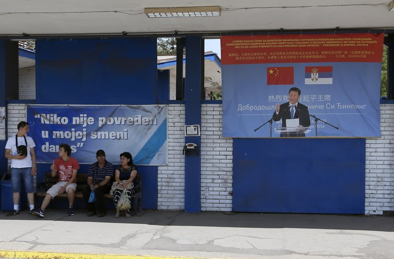 FILE - In this June 29, 2017, file photo, workers rest near billboard showing Chinese President Xi Jinping, reading: ''Welcome President'', right, and billboard reading: ''Nobody was hurt in my shift today'' in front of the Zelezara Smederevo steel mill, in the city of Smederevo, 45 kilometers east of Belgrade, Serbia. (AP Photo/Darko Vojinovic, File)