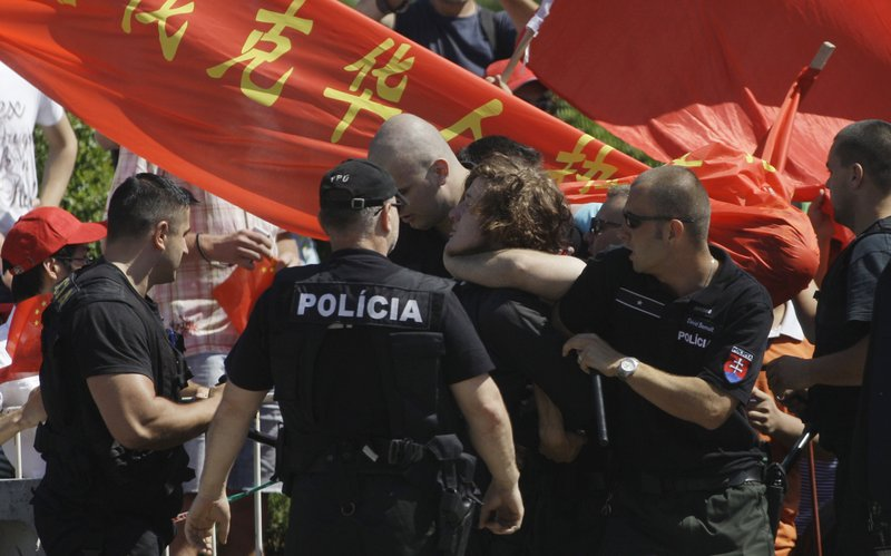 FILE - In this June 18, 2009, file photo, police arrests a human rights activist protesting against the Chinese government prior to the visit of Chinese President Hu Jintao, in front of the Presidential Palace in Bratislava, Slovakia. (AP Photo/Petr David Josek, File)