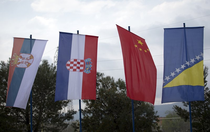 In this photo taken Tuesday, April 9, 2019, Serbian, Croatian, Chinese and the Bosnian flags at the trade fair in Mostar, Bosnia. (AP Photo/Darko Bandic)