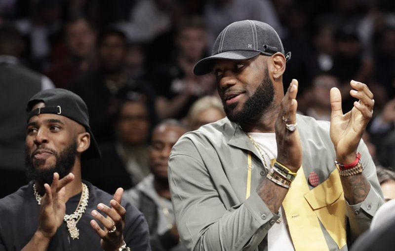 Chris Paul and LeBron James applaud during a ceremony at an NBA basketball game between the Brooklyn Nets and the Miami Heat, Wednesday, April 10, 2019, in New York. (AP Photo/Kathy Willens)