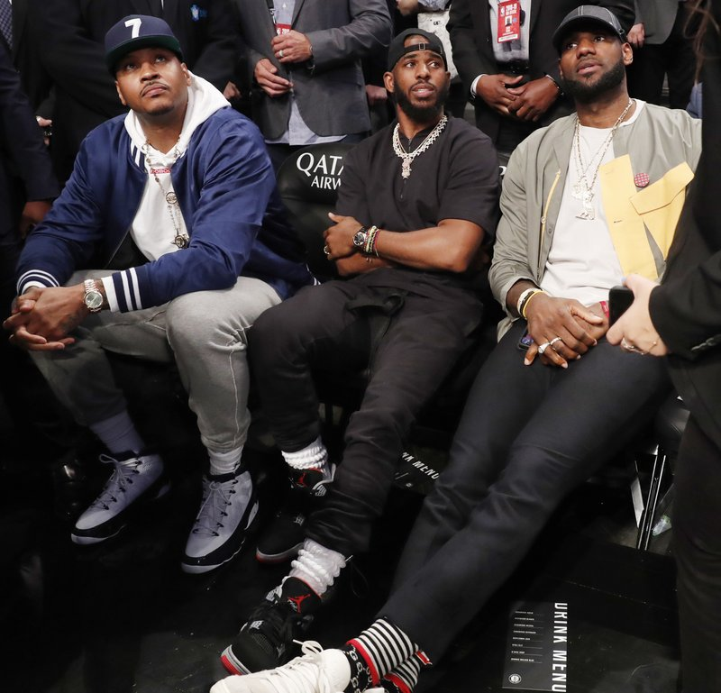 Carmelo Anthony, Chris Paul and LeBron James, from left, watch during the first half of an NBA basketball game between the Brooklyn Nets and the Miami Heat, Wednesday, April 10, 2019, in New York. (AP Photo/Kathy Willens)