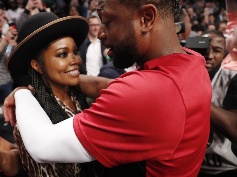 Miami Heat guard Dwyane Wade, left, has a few words with his wife, Gabrielle Union, before the team's BA basketball game against the Brooklyn Nets, Wednesday, April 10, 2019, in New York, Wade's final NBA game. (AP Photo/Kathy Willens)