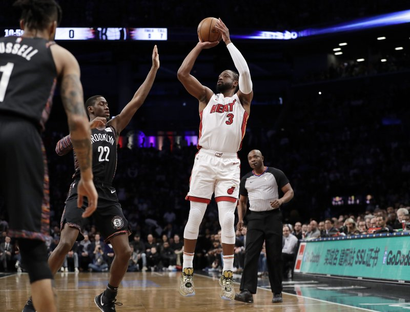 Brooklyn Nets guard Caris LeVert (22) defends as Miami Heat guard Dwyane Wade (3) shoots during the first half of an NBA basketball game Wednesday, April 10, 2019, in New York. (AP Photo/Kathy Willens)