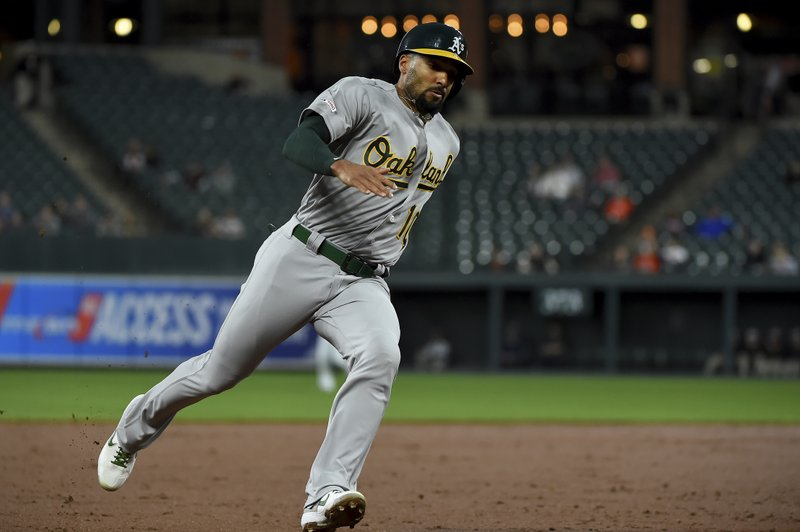 Oakland Athletics' Marcus Semien rounds third base to score on a double by Matt Chapman during the third inning of a baseball game against the Baltimore Orioles, Wednesday, April 10, 2019, in Baltimore. (AP Photo/Will Newton)