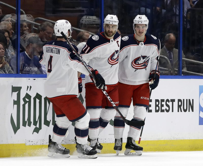 Columbus Blue Jackets left wing Nick Foligno (71) celebrates his goal against the Tampa Bay Lightning with center Alexandre Texier (42) and defenseman Scott Harrington (4) during the second period of Game 1 of an NHL Eastern Conference first-round hockey playoff series Wednesday, April 10, 2019, in Tampa, Fla. (AP Photo/Chris O'Meara)