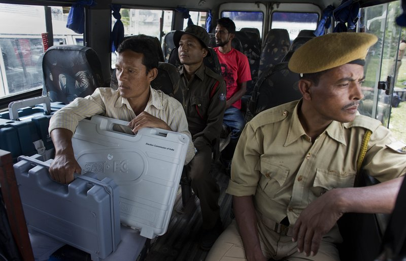 Indian polling officials and police with electronic voting machines and voter verifiable paper audit trail (VVPAT) sit inside a vehicle before heading to a polling station on the eve of the first phase of general election in Majuli, Assam, India, Wednesday, April 10, 2019. (AP Photo/Anupam Nath)