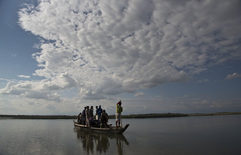 Indian election officials and paramilitary soldiers with election materials travel on a country boat to cross the river Brahmaputra on the eve of first phase of general election in Majuli, Assam, India, Wednesday, April 10, 2019. (AP Photo/Anupam Nath)