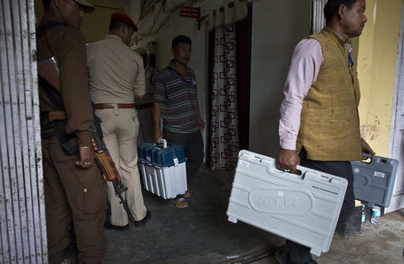 Indian polling officials carry electronic voting machines and voter verifiable paper audit trail (VVPAT) from a strong room to distribute on the eve of first phase of general election in Majuli, Assam, India, Wednesday, April 10, 2019. (AP Photo/Anupam Nath)