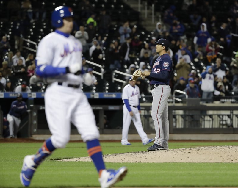Minnesota Twins' Andrew Vasquez stands on the mound as New York Mets' Brandon Nimmo, left, reaches first base after being hit by a pitch during a baseball game Wednesday, April 10, 2019, in New York. (AP Photo/Frank Franklin II)