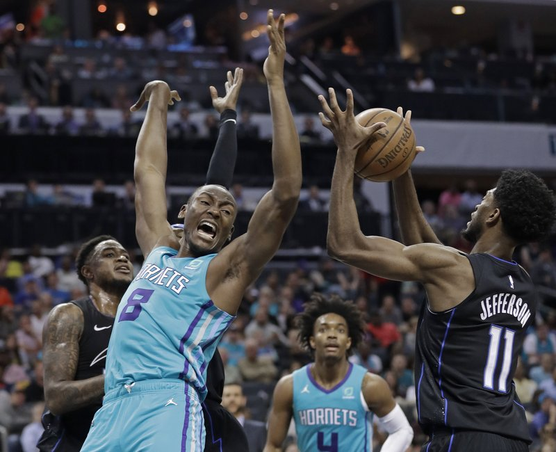 Charlotte Hornets' Bismack Biyombo (8) loses the ball as Orlando Magic's Amile Jefferson (11) and Jarell Martin defend during the first half of an NBA basketball game in Charlotte, N. (AP Photo/Chuck Burton)