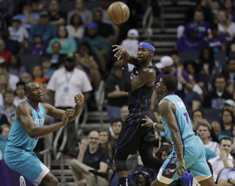 Orlando Magic's Terrence Ross, center, passes the ball as Charlotte Hornets' Bismack Biyombo, left, and Dwayne Bacon, right, defend during the first half of an NBA basketball game in Charlotte, N. (AP Photo/Chuck Burton)