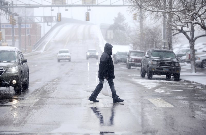 A pedestrian walks across Warren Avenue during a blizzard warning hitting southeast Wyoming and the Colorado Front Range on Wednesday, April 10, 2019, in Cheyenne, Wyo. (Jacob Byk/The Wyoming Tribune Eagle via AP)