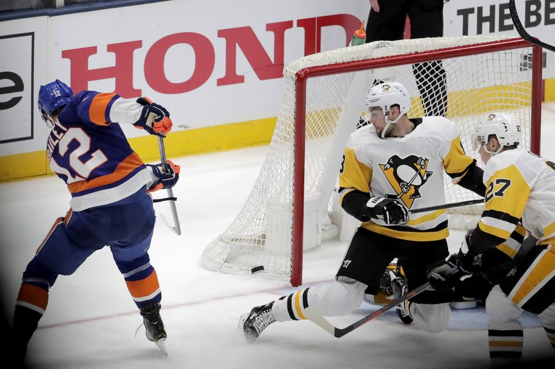 New York Islanders right wing Josh Bailey (12) scores during overtime of Game 1 of an NHL hockey first-round playoff series against the Pittsburgh Penguins, Wednesday, April 10, 2019, in Uniondale, N. (AP Photo/Julio Cortez)