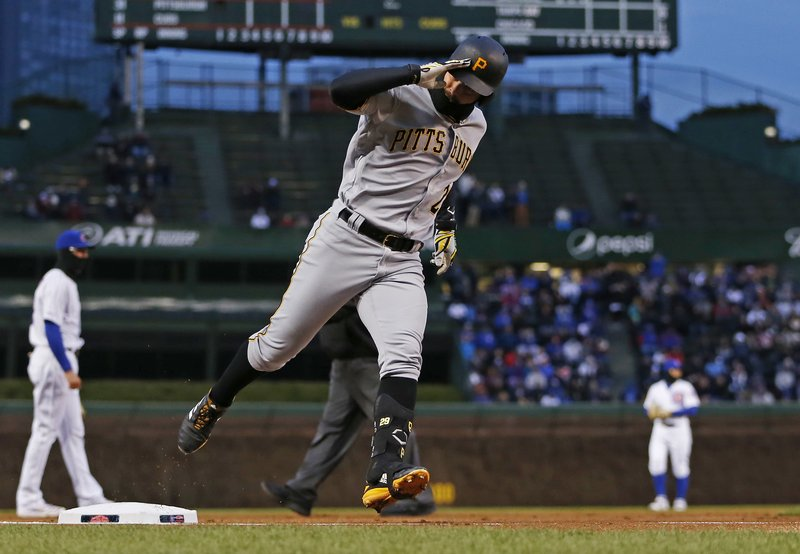 Pittsburgh Pirates' Francisco Cervelli reacts toward the Chicago Cubs dugout as he rounds third on a home run during the first inning of a baseball game in Chicago, Wednesday, April 10, 2019. (AP Photo/Nuccio DiNuzzo)