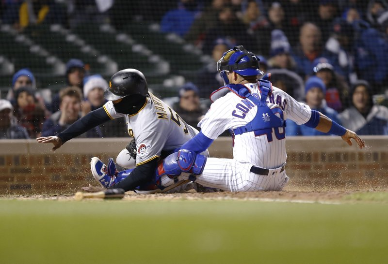 Pittsburgh Pirates Jason Martin is tagged out at home by Chicago Cubs catcher Willson Contreras during the seventh inning of a baseball game in Chicago, Wednesday, April 10, 2019. (AP Photo/Nuccio DiNuzzo)