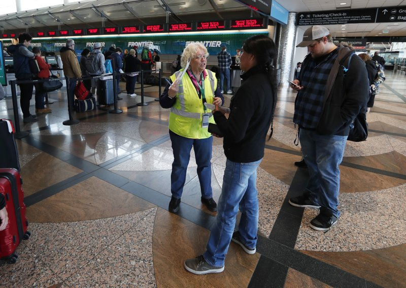 A Frontier Airlines representative talks with passengers as they wait to rebook their flights in Denver International Airport Wednesday, April 10, 2019, in Denver. (AP Photo/David Zalubowski)