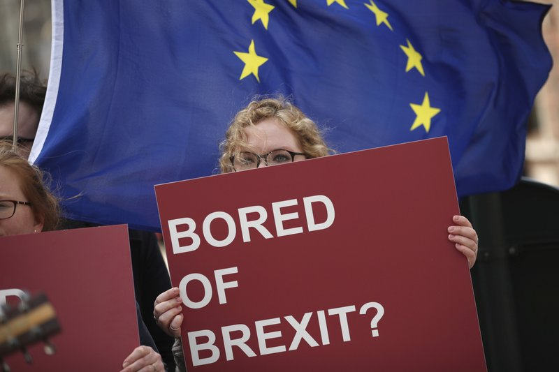 An anti-Brexit campaigner holds a sign in front of an EU flag during a protest outside EU headquarters in Brussels, Wednesday, April 10, 2019. (AP Photo/Francisco Seco)