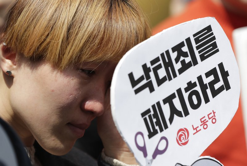 A woman wipes tears during a rally demanding the abolition of abortion law outside of the Constitutional Court in Seoul, South Korea, Thursday, April 11, 2019. (AP Photo/Lee Jin-man)