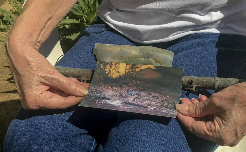 In this March 22, 2019, photo, Cheri Skipper, a Harbison Canyon resident, holds her burned flute and a picture showing what her home looked like after it burned during the Cedar Fire in 2003. (Ryan Sabalow/The Sacramento Bee via AP)