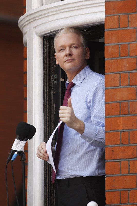FILE - In this Sunday, Aug. 19, 2012 file photo, WikiLeaks founder Julian Assange gestures as he appears at a window of Ecuadorian Embassy in central London to make a statement to the media and supporters. (AP Photo/Sang Tan, FIle)
