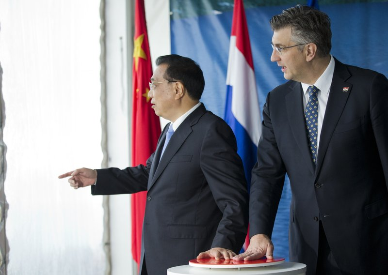 China's Premier Li Keqiang, left, and Croatia's Prime Minister Andrej Plenkovic, symbolically start a machine at the construction site of a bridge built by a Chinese company and largely EU founded, in Brijesta, Southern Croatia, Thursday, April 11, 2019. (AP Photo/Darko Bandic)