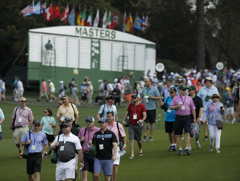 Fans walk near the first hole during the first round for the Masters golf tournament Thursday, April 11, 2019, in Augusta, Ga. (AP Photo/Charlie Riedel)