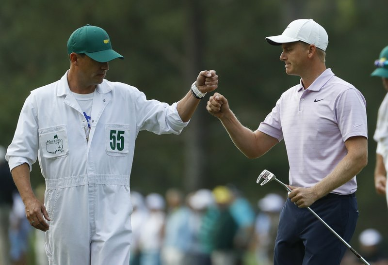 Adam Long reacts with caddie Matt Olson after making a putt on the third hole during the first round for the Masters golf tournament Thursday, April 11, 2019, in Augusta, Ga. (AP Photo/Matt Slocum)
