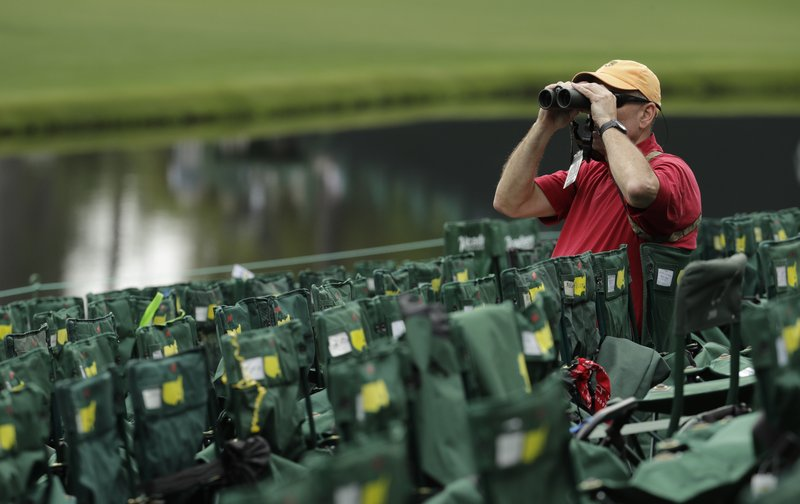 A fan watches on the 16th hole during the first round for the Masters golf tournament Thursday, April 11, 2019, in Augusta, Ga. (AP Photo/Charlie Riedel)