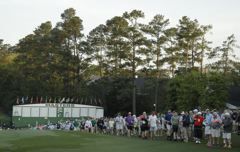 Fans walk along the first hole during the first round for the Masters golf tournament Thursday, April 11, 2019, in Augusta, Ga. (AP Photo/Charlie Riedel)