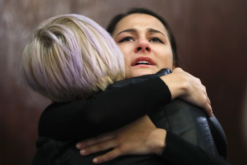 Bailey Kowalski hugs a friend after a news conference in East Lansing, Mich., Thursday, April 11, 2019. (AP Photo/Paul Sancya)