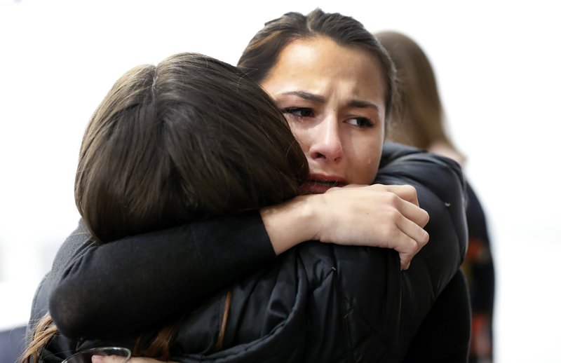 Bailey Kowalski hugs a friend before a news conference in East Lansing, Mich., Thursday, April 11, 2019. (AP Photo/Paul Sancya)