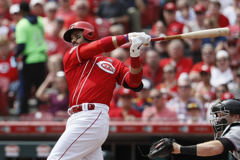 Cincinnati Reds' Eugenio Suarez hits an RBI single off Miami Marlins starting pitcher Pablo Lopez in the fourth inning of a baseball game, Thursday, April 11, 2019, in Cincinnati. (AP Photo/John Minchillo)
