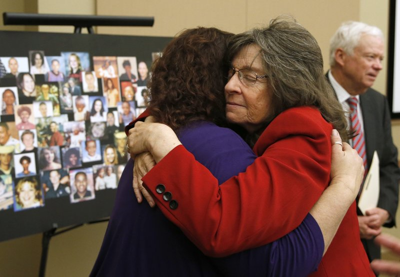 Sandy Friend, the mother of 8-year-old murder victim Michael Lyons, left, and Raquel Herr, the mother of murder victim Sam Herr, comfort each other after a news conference to call on Gov. (AP Photo/Rich Pedroncelli)
