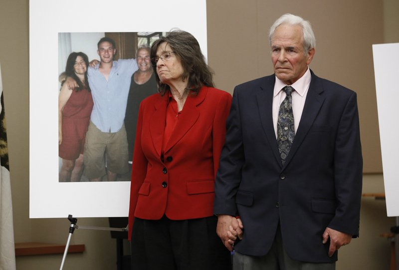 Steve Herr, right, accompanied by his wife, Raquel, the parents of murder victim Sam Herr, stand next to a photo of there late son at a news conference to call on Gov. (AP Photo/Rich Pedroncelli)